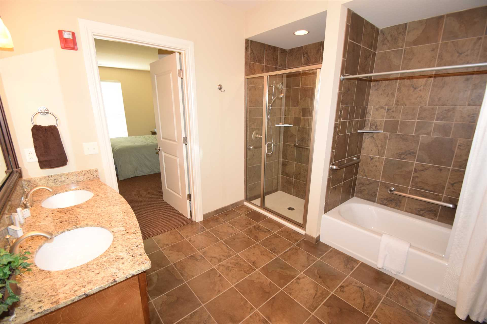 This spacious bathroom includes a tub and a walk-in shower.