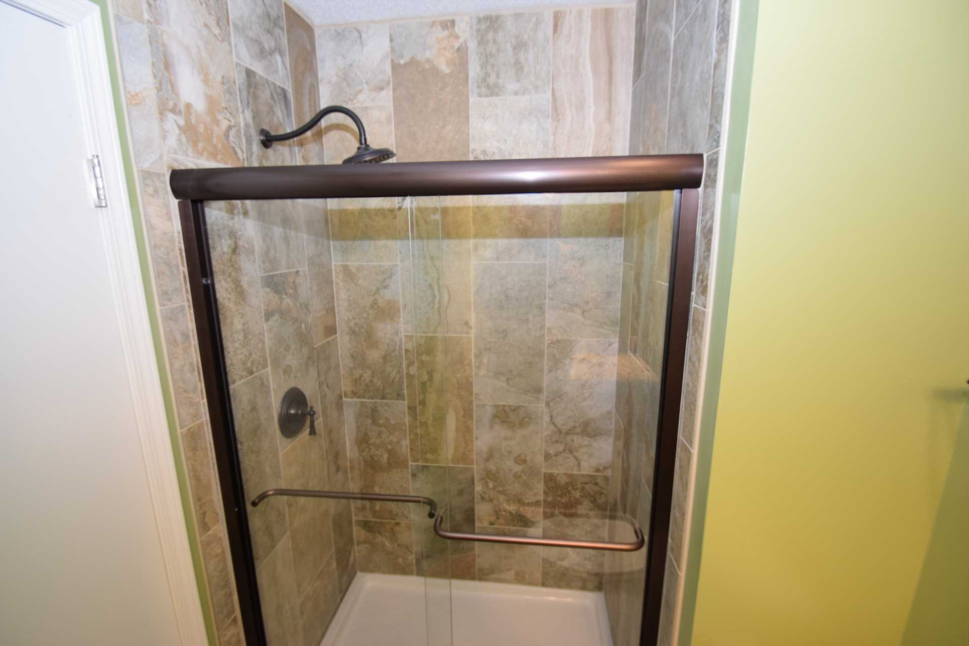 The master bath has a fancy tiled shower with tall fixtures