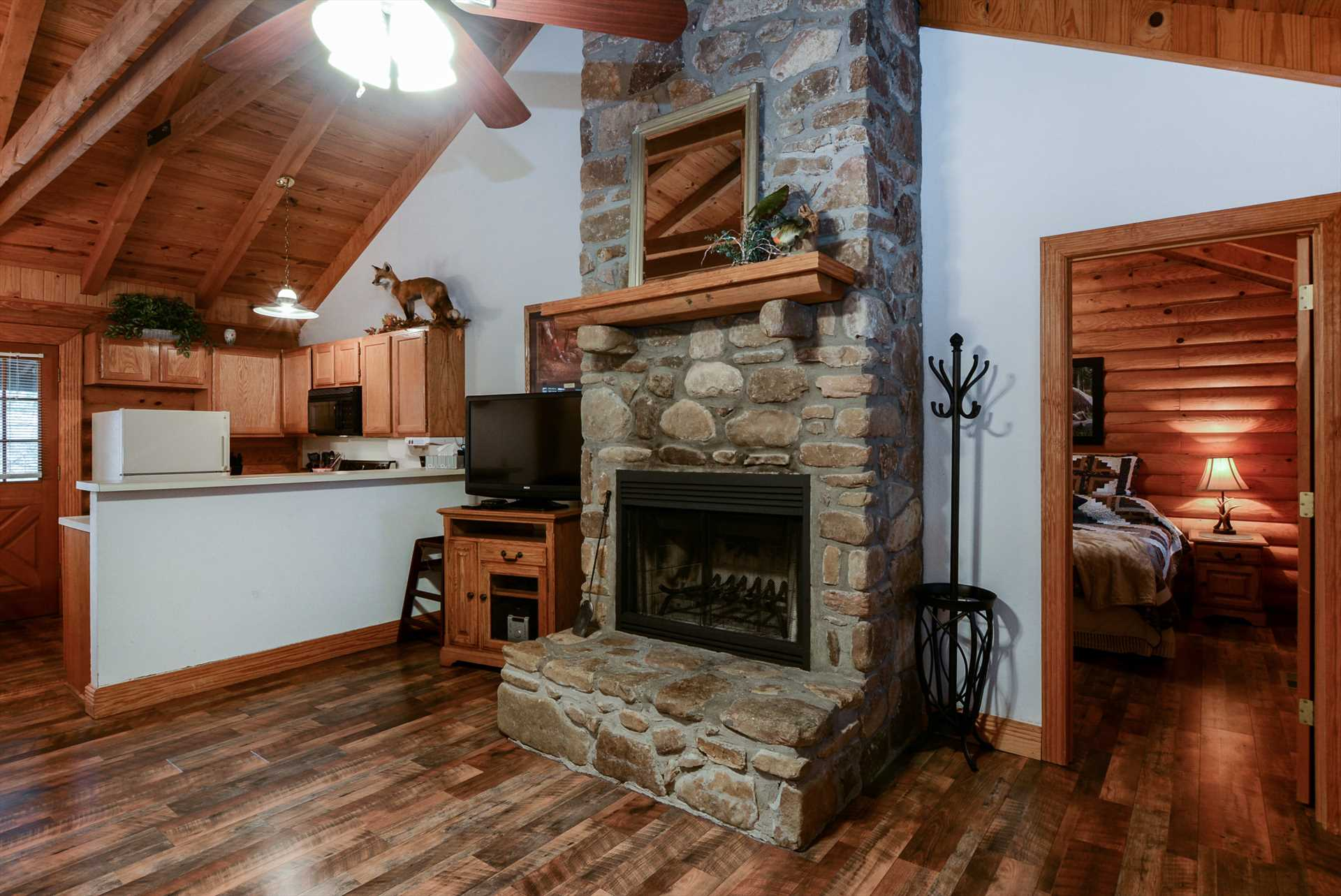 The stone fireplace is the centerpiece of the living area.