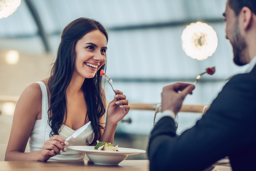 Young couple smiling, enjoying a meal in a nice restaurant