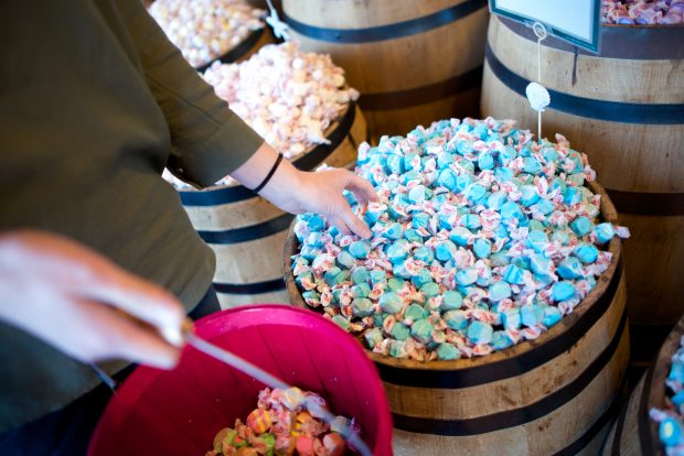 A woman reaches for blue salt water taffy in barrel